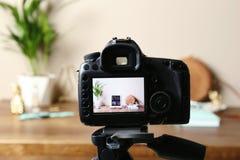 Camera with photo of stylish workplace on screen indoors. Fashion blogger. Camera with photo of stylish workplace on screen indoors, selective focus. Fashion royalty free stock image