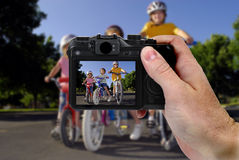 Camera Picture of Girls Riding Bikes. Hand holding camera taking a picture of little girls riding bikes Royalty Free Stock Image