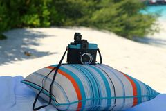 Camera on the pillow on the beach royalty free stock images