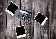 Camera and polaroid photos. Old film camera and polaroid photos with space for pictures on the wooden background Stock Photography
