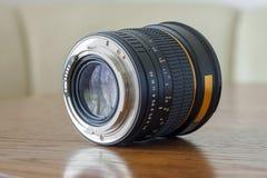 Camera portrait fix focus photo lens on dark wooden background.  stock images