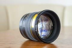 Camera portrait fix focus photo lens on dark wooden background.  Stock Image