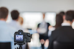 Camera at press conference. Camera on tripod at press conference of business people Stock Photo