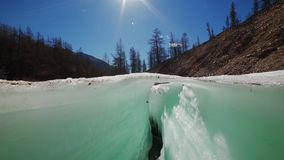 Camera raising above the ice crack in spring. Camera raising by slider above the blue ice crack with a running creek under it on a sunny day stock video footage