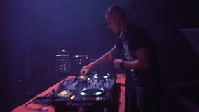 Camera rapidly zooming in and out on dj playing music at night club party stock video footage