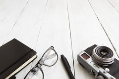 Camera, reading glasses, notepad and pan on wooden background - Stock Photography