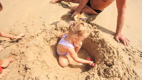 Camera Removes from Grandpa Kids Play among Sand Heap on Beach stock video
