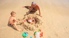 Camera Removes from Grandpa Kids Play among Sand Heap on Beach stock video footage