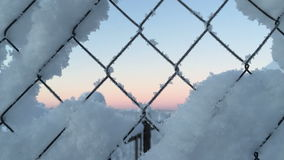 Camera removes the mesh fence covered with snow then moves away. stock footage