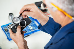 Camera Repair. Repairman checking Old Rangefinder Camera Stock Images