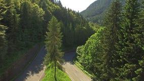Camera rising above serpentine road at summer stock video