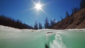 Camera rising above the ice crack. Camera rising by slider above the blue ice crack with a running creek under it on a sunny day stock video footage