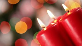 Camera rotating in front of three xmas candles burning stock footage