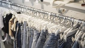 Camera run across a rack of clothes, browsing in a boutique. Head-on view with rack focus.
