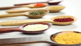 Camera selective focus over assortment of spices in wooden spoons stock footage