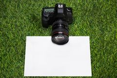 Camera with sheet of paper lying on grass Royalty Free Stock Images