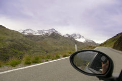 Camera shooting mountain on road from car. Mirror reflection of lens and photographer hand Stock Photography
