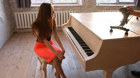 Camera shooting from the slider of beautiful young woman model in musical interior. Model in dress is sitting near the grand piano with open keys stock video