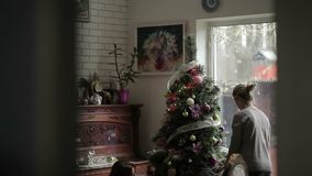 Two sisters decorates Christmas tree in the home. The camera shoots from behind the wall. Two beautiful sisters decorating the Christmas tree. Beautiful young stock video footage