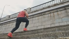 Athletic man jumps at the stairs. The camera shoots from below. Young sporty brunette man is at the embankment. Attractive young man wearing outfit starts to stock video footage