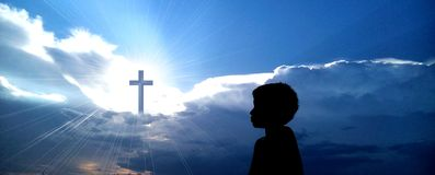 Christian cross with boy praying. Camera shot on a Christian cross with boy praying Royalty Free Stock Photography