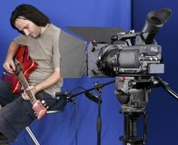Camera shot the gutarman. Black high definition camcorder shot the guitarman in studio with blue background Royalty Free Stock Photo