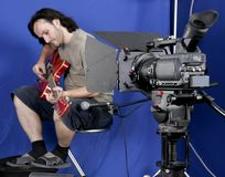 Camera shot the gutarman. Black high definition camcorder shot the guitarman in studio with blue background Royalty Free Stock Images