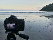Camera showing person on an empty beach at sunset Stock Photo