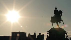 Silhouettes of monument, group of people standing underneath and jumping bikers. stock video