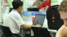 Camera Shows Asian Man Changes Focus to Man Looking at Monitor. KAZAN TATARSTAN/RUSSIA - MAY 15 2013: Camera shows asian man at computer and changes focus to stock video