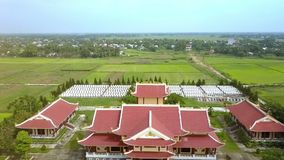 Camera Shows Buddhists Temple and Neat Cemetery against Fields. Camera shows wonderful buddhists temple with beautiful pagodas and neat cemetery against wide stock video