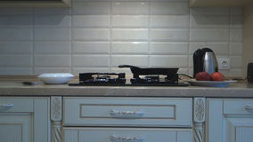 The camera shows the kitchen with furniture and a gas stove. The camera slowly turns around and shows the kitchen with furniture and a gas stove stock footage
