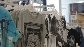 Camera shows male t-shirts with stylish prints in store stock video footage