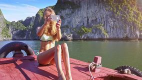 Camera Shows Girl Making Selfie against Tranquil Bay and Rocks stock video