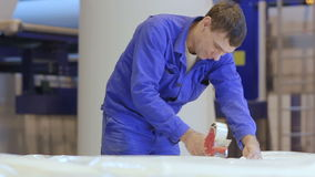 Camera Shows Worker Packing Foam Rubber with Adhesive Tape. KAZAN, TATARSTAN /RUSSIA - JANUARY 15 2015: Camera moves down and shows worker in uniform packing stock video footage