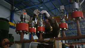 Camera Shows Worker Twisting Screw on Pipeline Top. KAZAN, TATARSTAN/RUSSIA - DECEMBER 20 2016: Camera shows professional worker twisting screw with tool on stock video footage