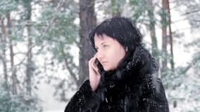 The camera slider moves around a woman standing against a park or forest on a winter snowy day. A brunette girl in a stock footage