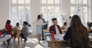 Camera slides left along trendy loft office, happy multiethnic business partners working at modern workplace atmosphere. Positive corporate managers cooperate stock video footage