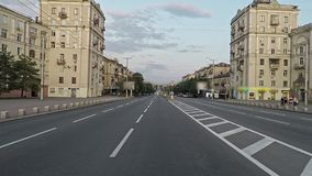 Camera smoothly cross the wide empty street of the evening city