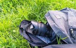 The camera sticks out of a backpack lying on the grass close-up stock image