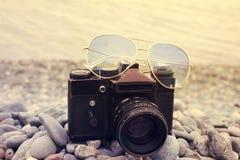 Camera with sun glasses close up shoot on a sea beach. Retro vac stock image