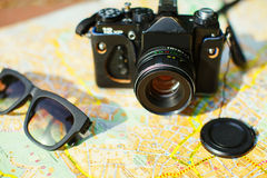 camera and sunglasses on the tourist map Stock Images