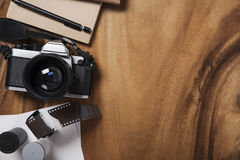 Camera and supplies, Blank photo on wooden table Royalty Free Stock Image