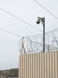 Camera surveillance and barbed wire Stock Photography