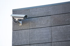 Camera system guarding blue skyscraper office building with blue sky above in horizontal format Stock Image