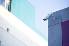 Camera system guarding blue skyscraper office building with blue sky above in horizontal format Royalty Free Stock Photos