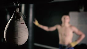 Camera takes a close-up pneumatic punching bag. The camera takes a close-up pneumatic punching bag. Young man standing near the adjacent punching bag on blurred stock footage