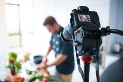 The camera takes off the cooking process of a man. The camera takes off the cooking process in the kitchen of a European brunette man Stock Photo