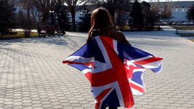 Camera To Girl, Wrapped In Union Jack Flag and. Turning around stock video footage