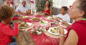 Camera tracks around table as extended family group enjoy Christmas meal together. Family With Grandparents Enjoying Christmas Meal Shot On R3D stock footage